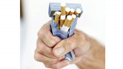 close-up of a man's hand crushing a pack of cigarettes