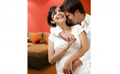 man-and-pregnant-woman-laughing-as-they-hold-each-other